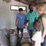 Project Managers Corey Spies (left) and Brianna Parsons (right) meet with a Gambian smallholder farmer to learn about feed sourcing in The Gambia