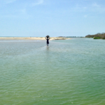 A fisherman in Tanji Village wades through a tidal pool